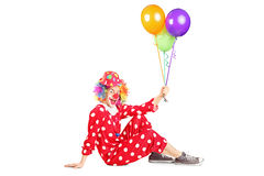 Clown holding balloons seated on the floor Royalty Free Stock Photo