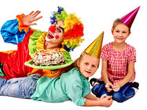 Clown holding cake on birthday with group children Royalty Free Stock Image