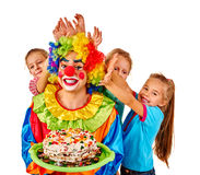 Clown holding cake on birthday with group children. Stock Photos