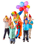Clown holding cake on birthday with group children. Stock Photo