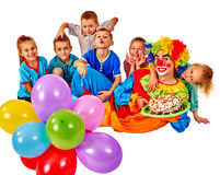 Clown holding cake on birthday with group children. Royalty Free Stock Image