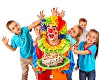 Clown holding cake on birthday with group children Stock Photos