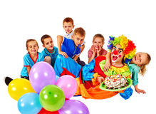 Clown holding cake on birthday with group children Stock Image