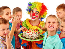 Clown holding cake on birthday with group children Stock Photo