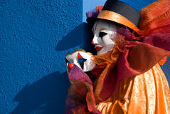 Clown holding mask in front of blue wall Royalty Free Stock Photos