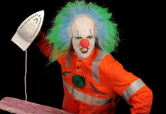Clown with iron. Menacing clown in full costume with iron royalty free stock photography