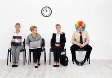 Clown among job candidates. There's one in every crowd - clown among job candidates waiting Royalty Free Stock Image
