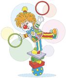 Clown juggler and equilibrist. Circus show of a funny juggler - equilibrist. Friendly smiling circus comic balancing on several objects and juggling with hoops Stock Images
