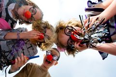 Clown kids. A group of kids looking down at the camera with silly glasses and clown noses Royalty Free Stock Images