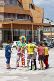 Clown and kids on the street. Clown making balloon animals and shapes for the kids on the street Stock Photography