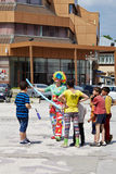 Clown and kids on the street. Clown making balloon animals and shapes for the kids on the street Stock Images
