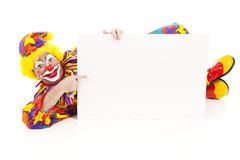 Clown Lies Down With Sign Stock Photography