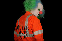 Clown looking over shoulder. Rear view portrait of man in scary clown mask wearing fluorescent jacket looking over shoulder, isolated on black background stock images