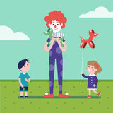 Clown is making balloon animals for girl and boy Royalty Free Stock Photos