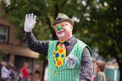 Clown in mano d'ondeggiamento verde del cappello e del costume fotografia stock