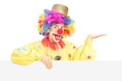 Clown masculin de sourire se tenant derrière le panneau vide faisant des gestes avec l'ha Images libres de droits