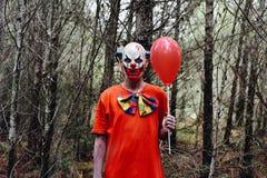 Clown mauvais effrayant dans les bois photographie stock libre de droits