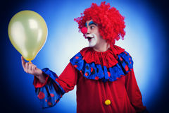 Clown men with a ballon on blue background Stock Images