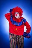 Clown men thinking in studio blue background Royalty Free Stock Photo