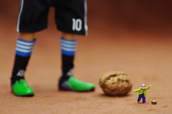 Clown and Messi. A clown is ready for kicking mung, while a soccer player is ready for kicking a walnut Royalty Free Stock Photography