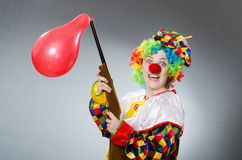 Clown met ballon en geweer in grappig concept Stock Afbeelding