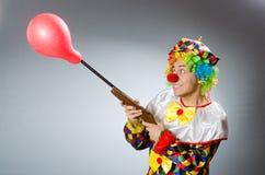 Clown met ballon en geweer in grappig concept Stock Afbeeldingen
