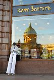 Clown-MIME on stilts sits on the window of the Caf singer in t. He background reflection of the Kazan Cathedral. inscription: cafe singer Royalty Free Stock Image