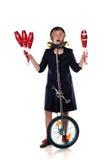 Clown mit jonglierenden Vereinen und einem Unicycle Stockfotos