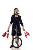 Clown mit jonglierenden Vereinen und einem Unicycle Lizenzfreie Stockbilder