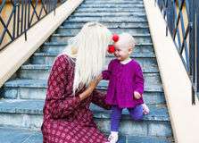 Clown-mother: red nose contact with baby daughter. Stock Photography