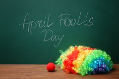 Clown nose and rainbow wig on table near chalkboard. With written phrase `April fool`s day Royalty Free Stock Photo