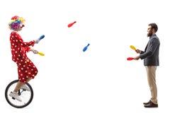 Clown op unicycle het jongleren met met een gebaarde mens royalty-vrije stock afbeeldingen