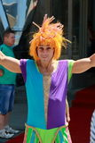 Clown with orange wig near entrance to the circus Stock Image