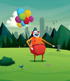 Clown in park laughing with balloon Royalty Free Stock Image