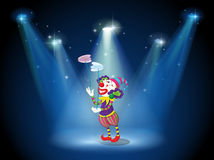 A clown performing on a stage under the spotlights Stock Photography