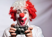 Clown photographer. Clown with vintage , old fashioned camera on a white  backgruond Royalty Free Stock Photography