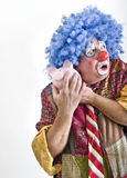 Clown piggybank. Clown holding a piggy bank isolated on white Stock Images