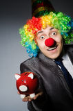 Clown with piggybank Stock Photo