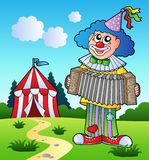 Clown playing accordion near tent Stock Photo