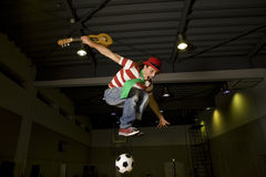 A clown playing guitar and soccer Stock Image