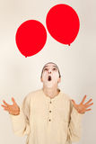 The clown is playing with red balloons Royalty Free Stock Photo