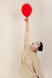 The clown is playing with red balloons Stock Images