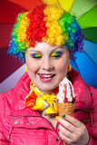 Clown with rainbow make up eating ice cream. Beautiful woman in rainbow clown wig with freckles and creative rainbow make-up holding strawberry ice cream and Stock Photos