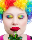 Clown with rainbow make up smelling rose. Beautiful woman in rainbow clown wig and creative rainbow make-up smelling red rose at white background Royalty Free Stock Photo