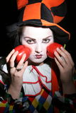 Clown with red peppers. Teenage female clown in costume with two red peppers, black background Stock Image