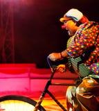 Clown riding bicycle Stock Photos
