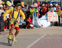 Clown riding unicycle in a public square Royalty Free Stock Images