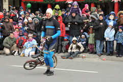 Clown at the Santa Parade. Cheerful crowd appreciates the clown on the mini bicycle....during a Christmas parade Stock Photo