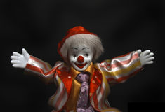 Clown says: Hey. Porcelain clown with open arms on black background Stock Image