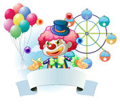A clown with a signage and a ferris wheel and balloons at the ba Stock Image